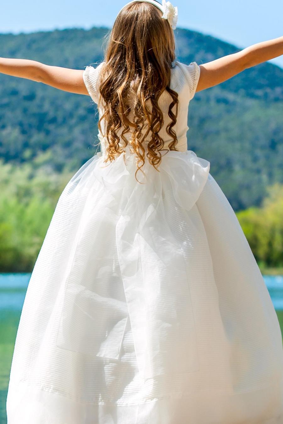 Niña con vestido blanco abriendo los brazos y viendo hacia un lago