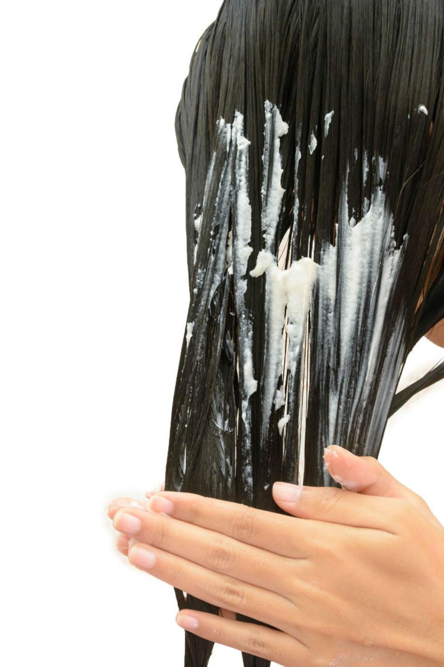 mujer con cabello negro aplicándose un producto en el pelo