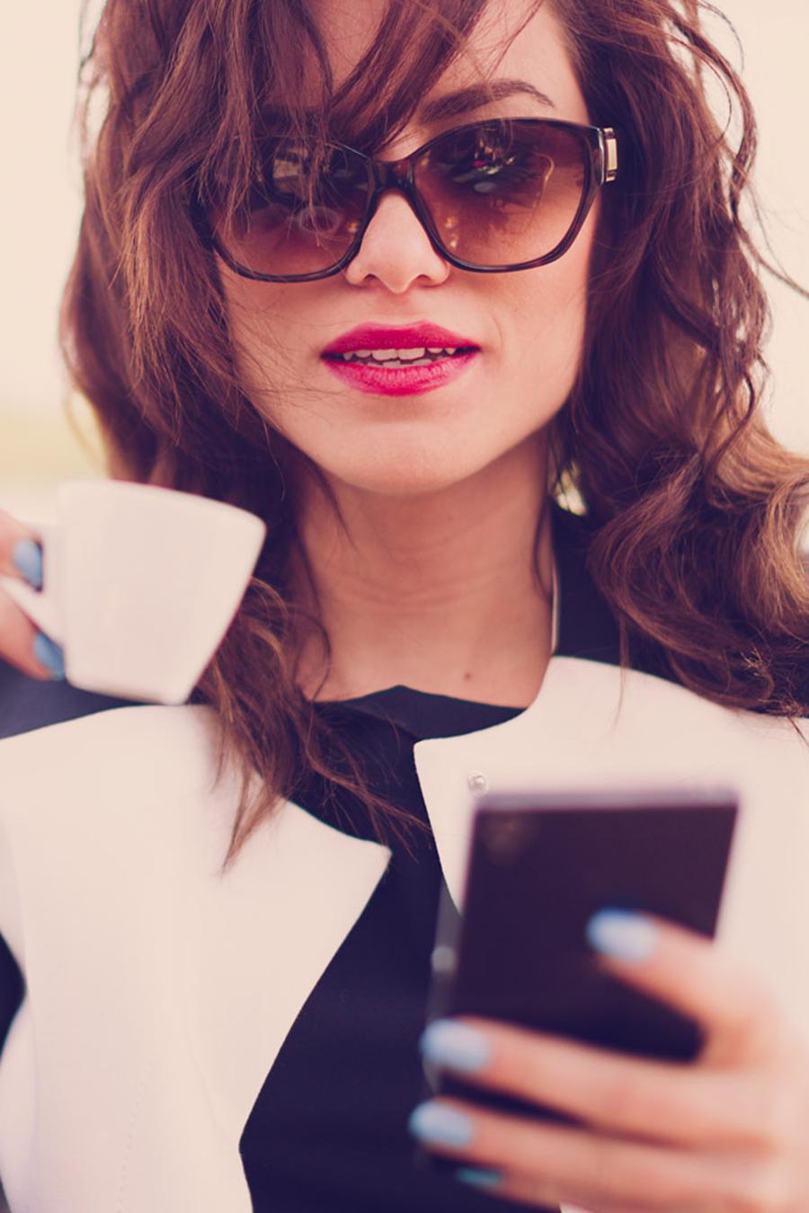 Mujer bebiendo café y sosteniendo un celular