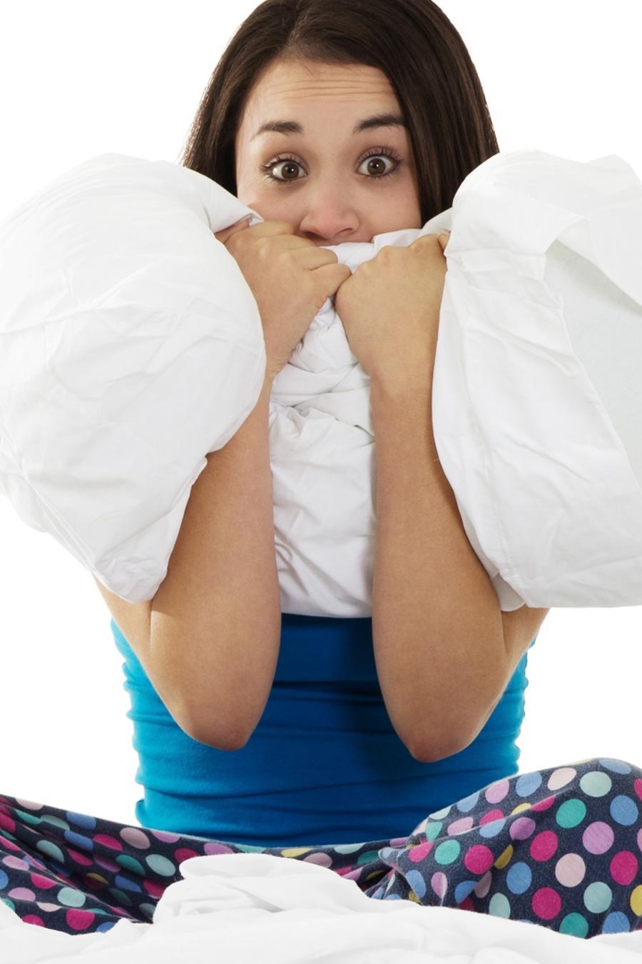 Mujer asustada sentada en la cama y sosteniendo una almohada