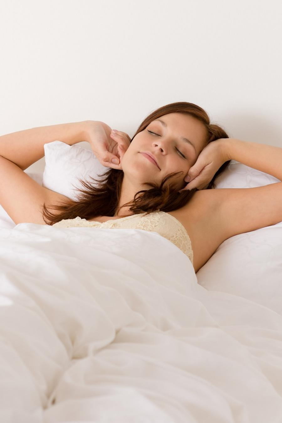 Mujer acostada en una cama cubierta con sábanas blancas