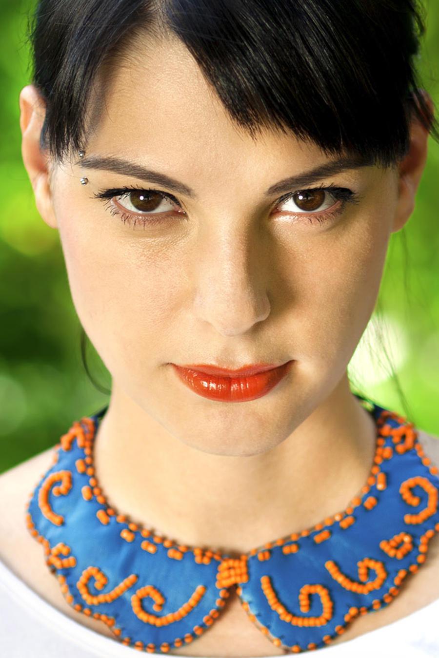 Mujer de ojos marrones con cabello recogido y collar azul