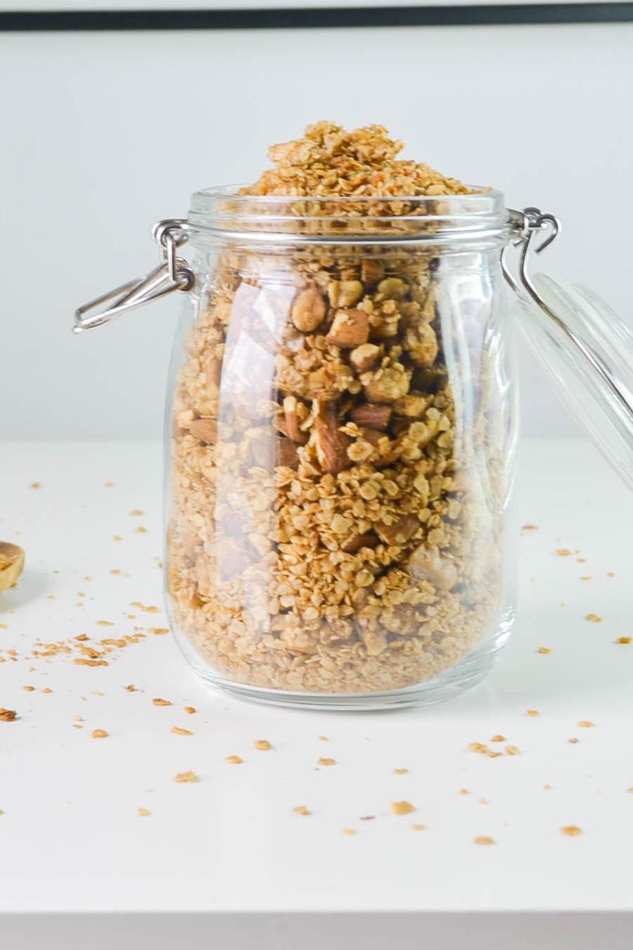 Envase de vidrio con granola y cuchara de madera