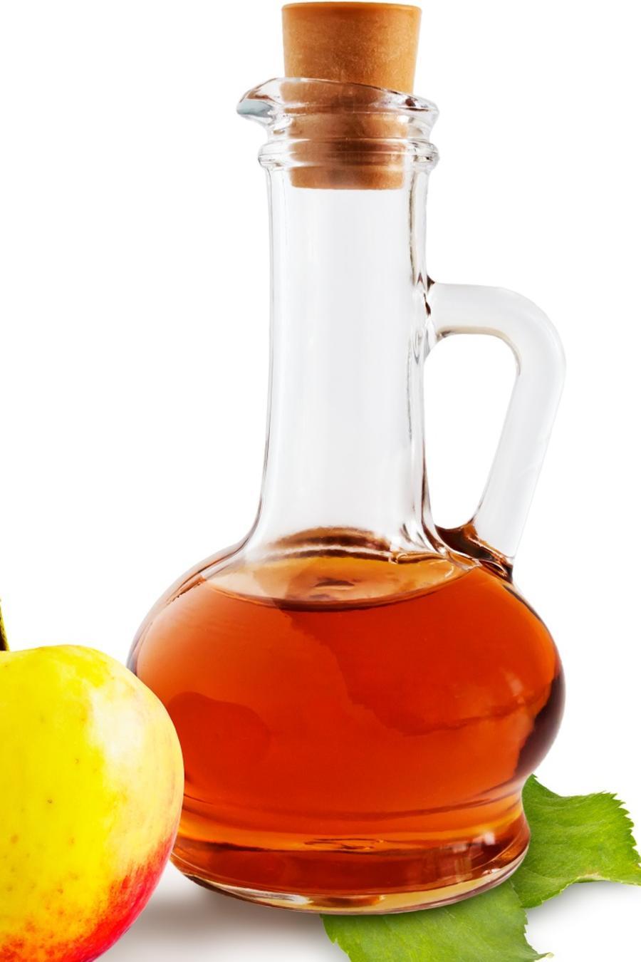 Botella de vinagre al lado de una manzana
