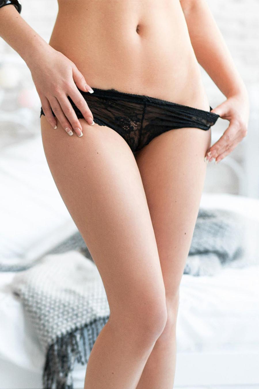 Mujer con ropa interior negra de pie frente a la cama