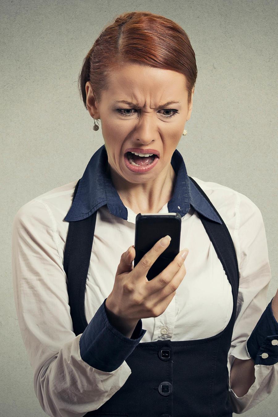 Mujer con cara de disgusto viendo el teléfono celular y sosteniendo un corazón