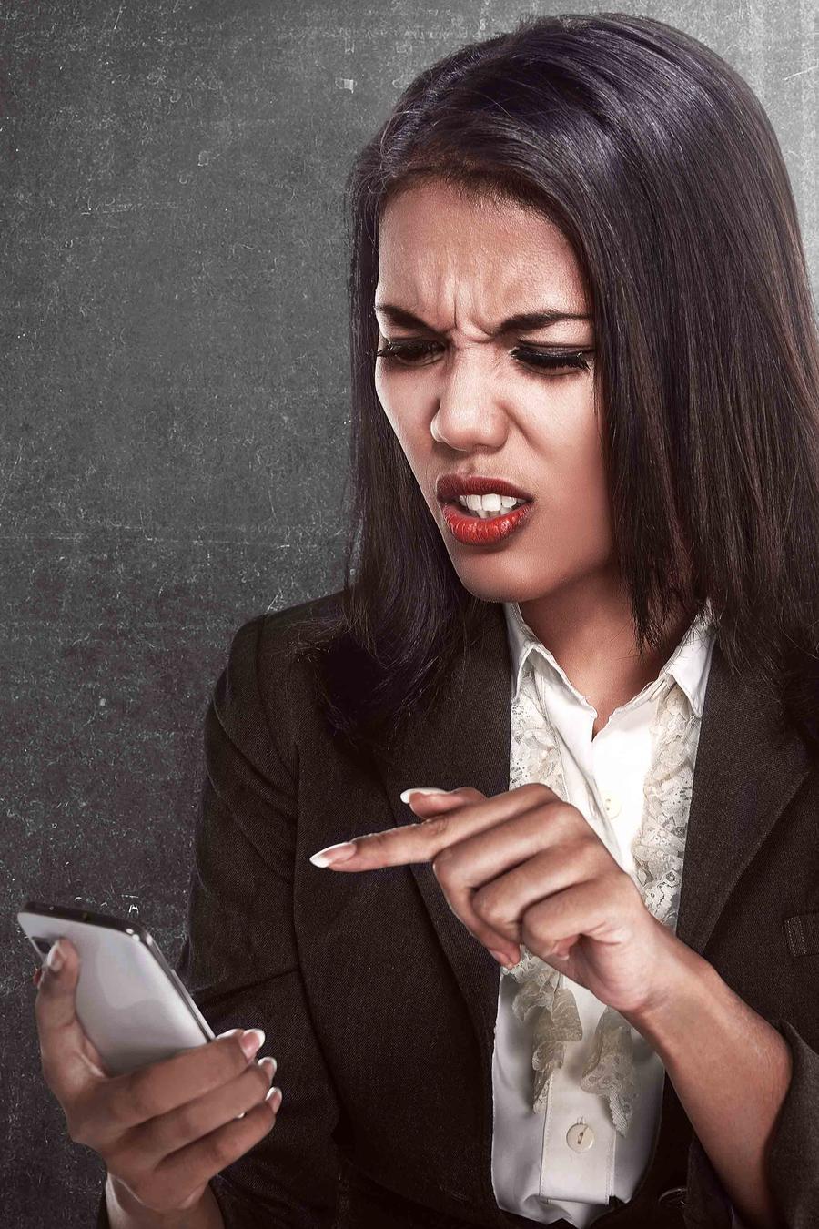 Mujer mirando la pantalla del celular con cara de disgusto