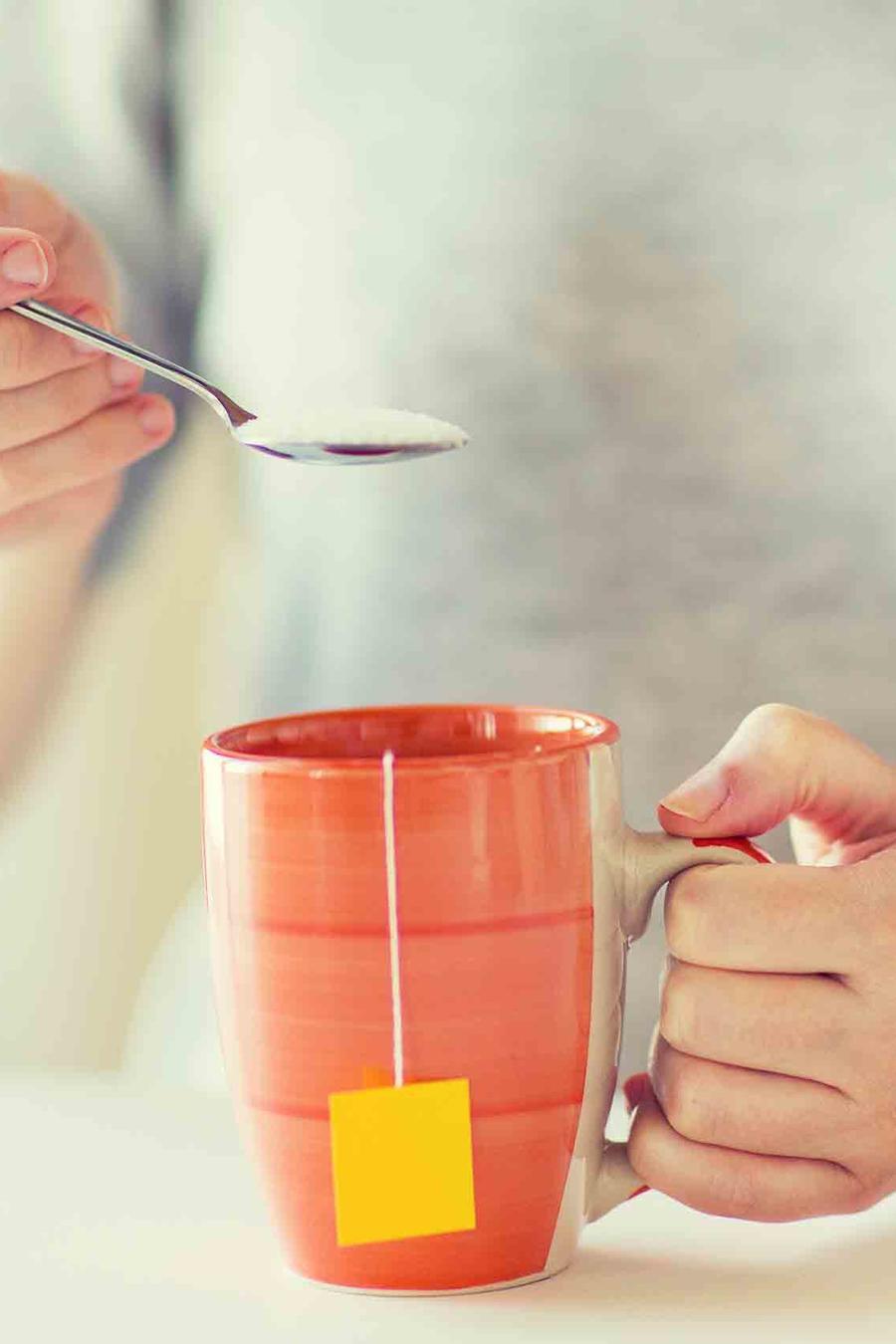 Mujer sosteniendo taza de te y cuchara