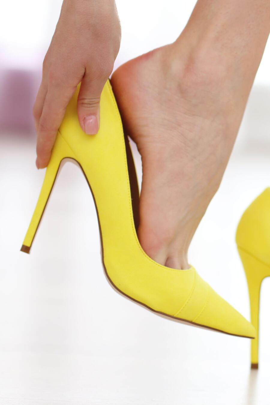 Piernas de mujer con zapatos amarillos de tacón