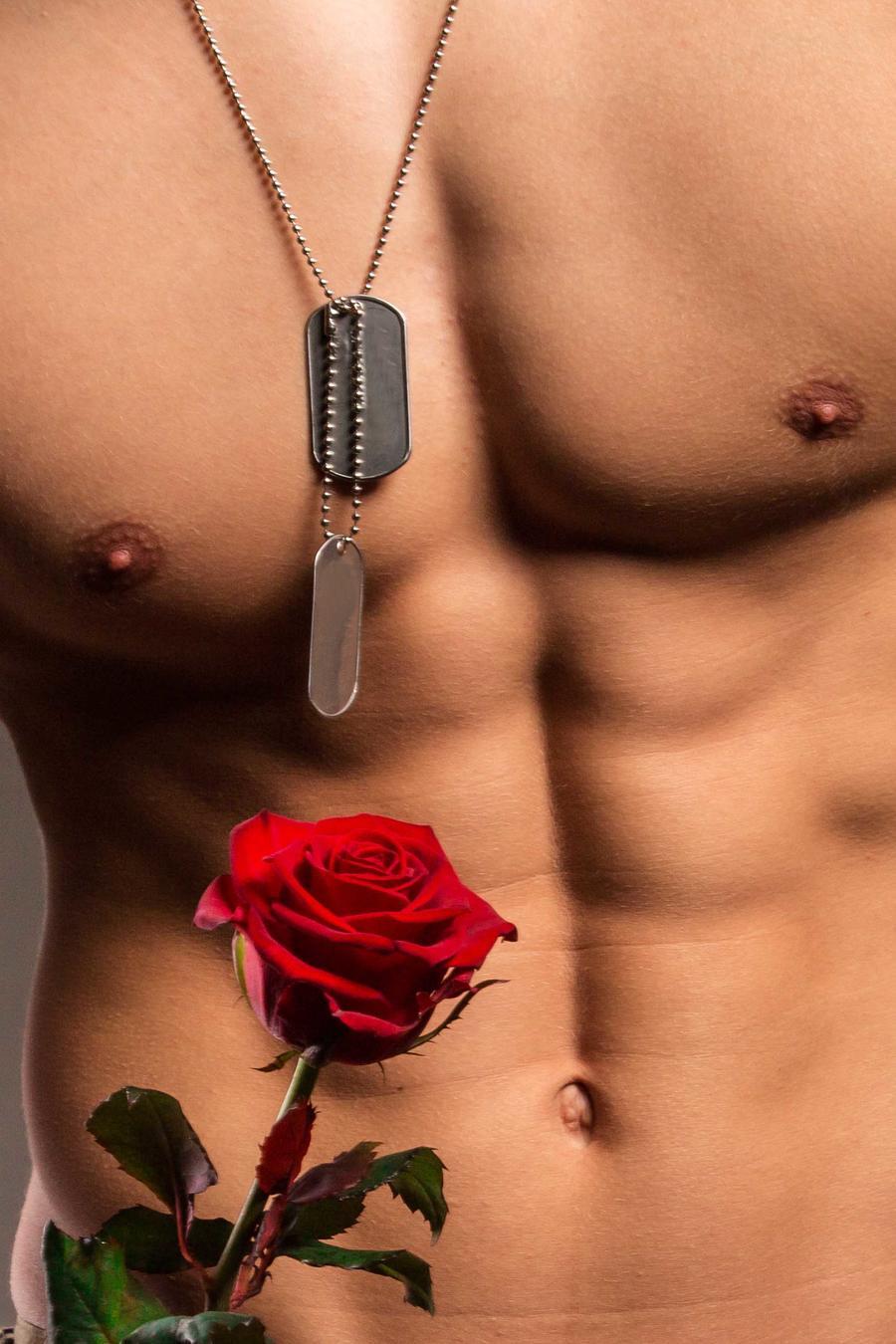 Hombre con abdominales marcados sosteniendo una rosa roja