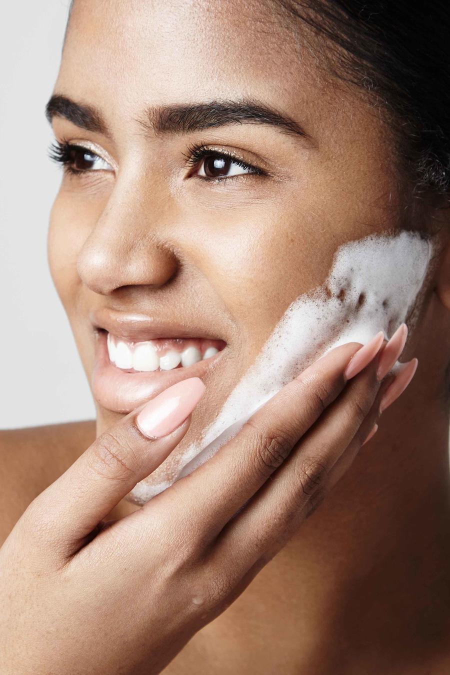 Mujer aplicándose espuma en la cara