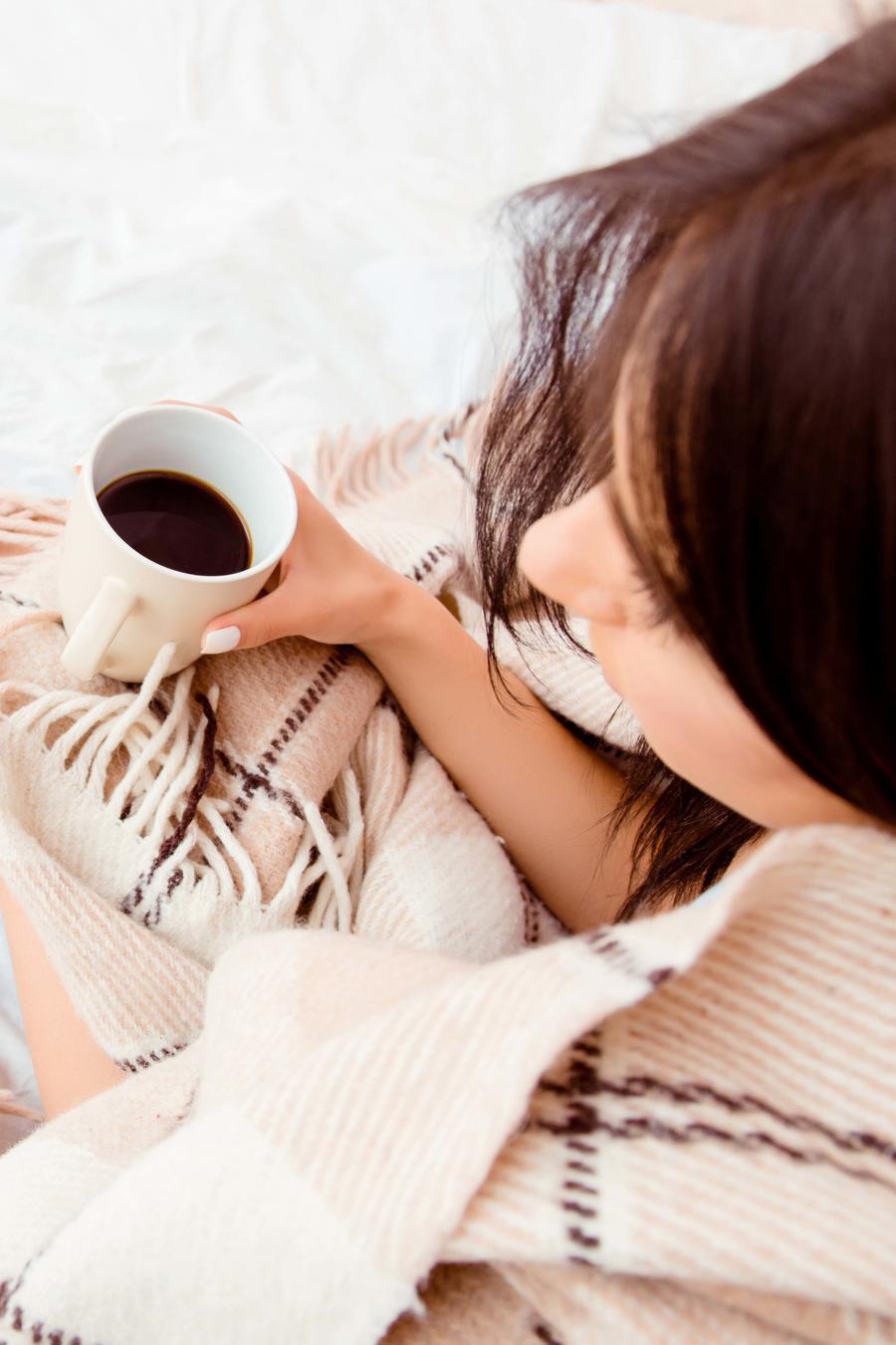 Mujer tomando te y leyendo un libro en la cama