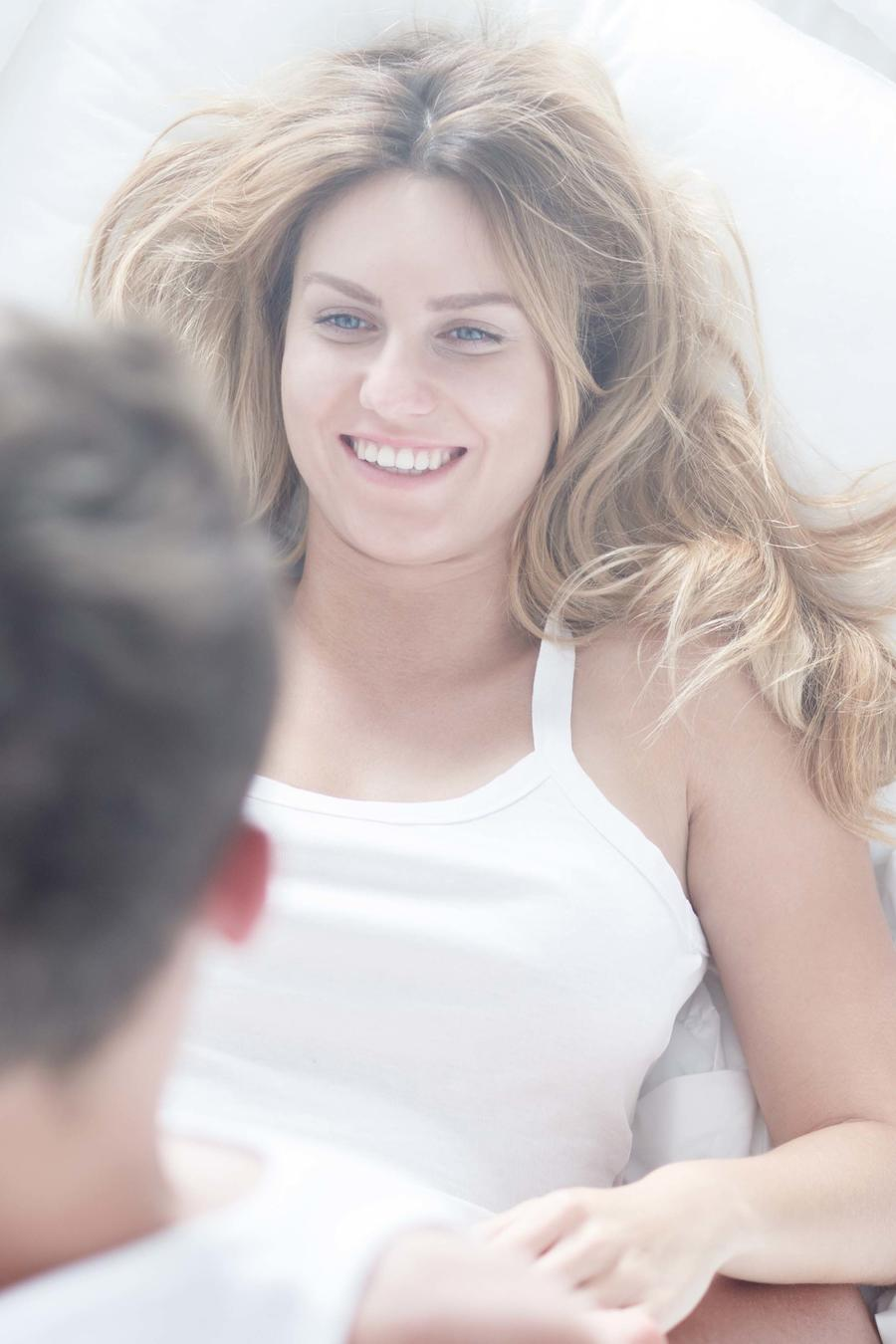 Pareja jugueteando en la cama sobre sábanas blancas