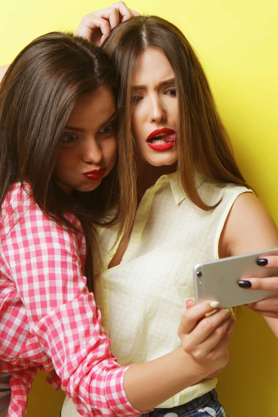Amigas haciéndose un selfie con muecas en fondeo amarillo