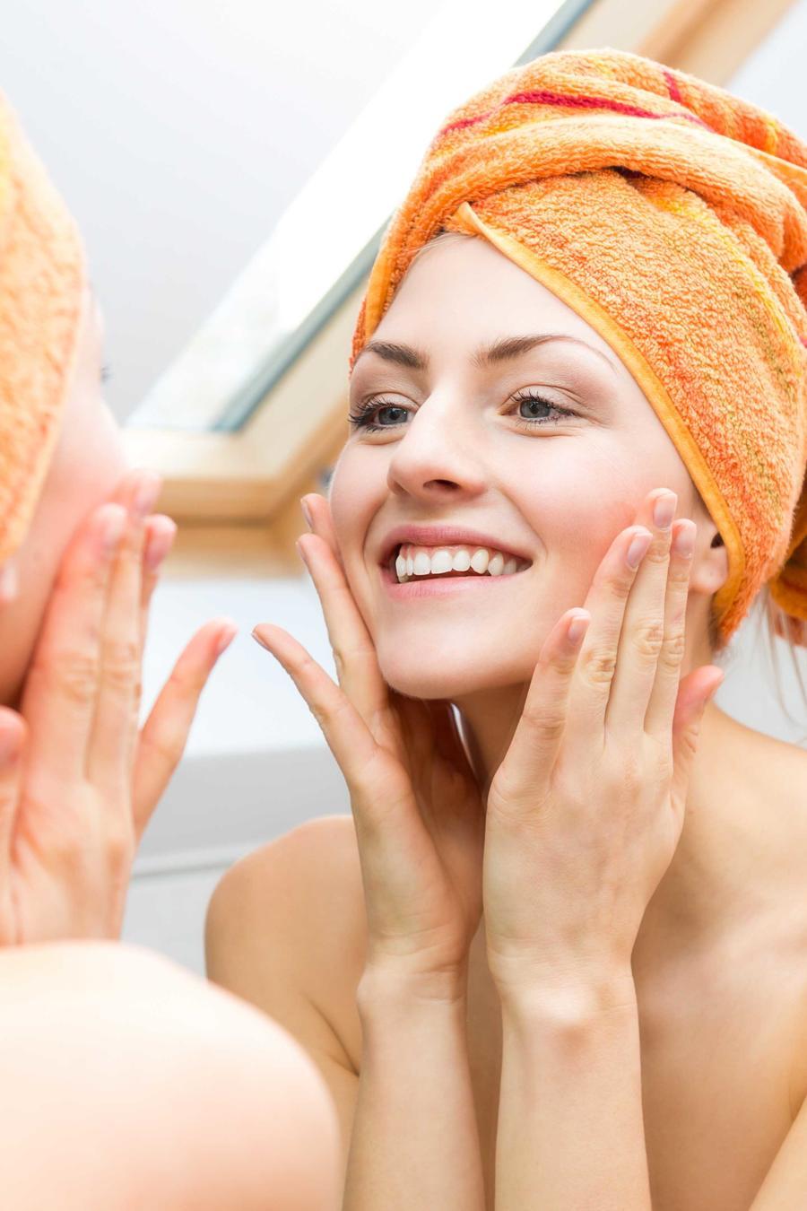 Mujer frente al espejo tocándose el rostro