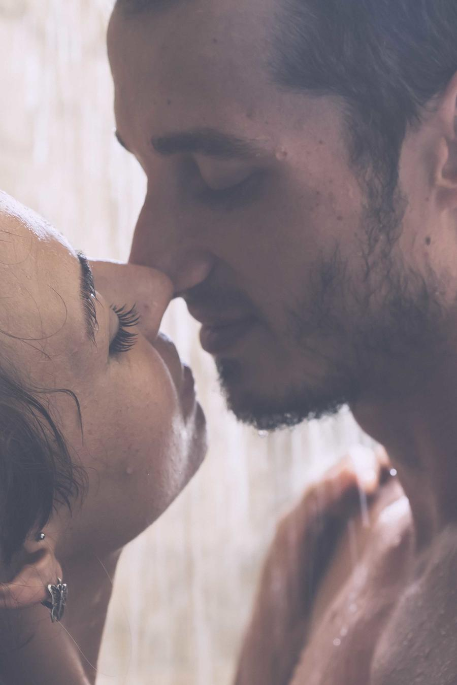 Pareja besándose bajo la ducha