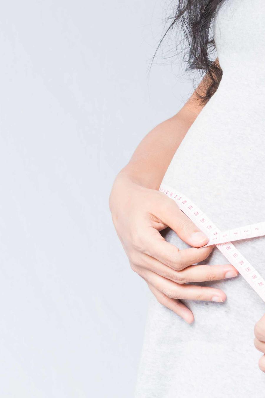 Embarazada midiéndose la barriga con cinta métrica