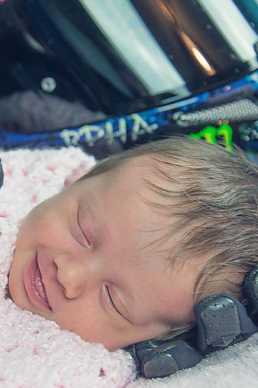 Foto de una bebé sostenida por los guantes de moto de su padre