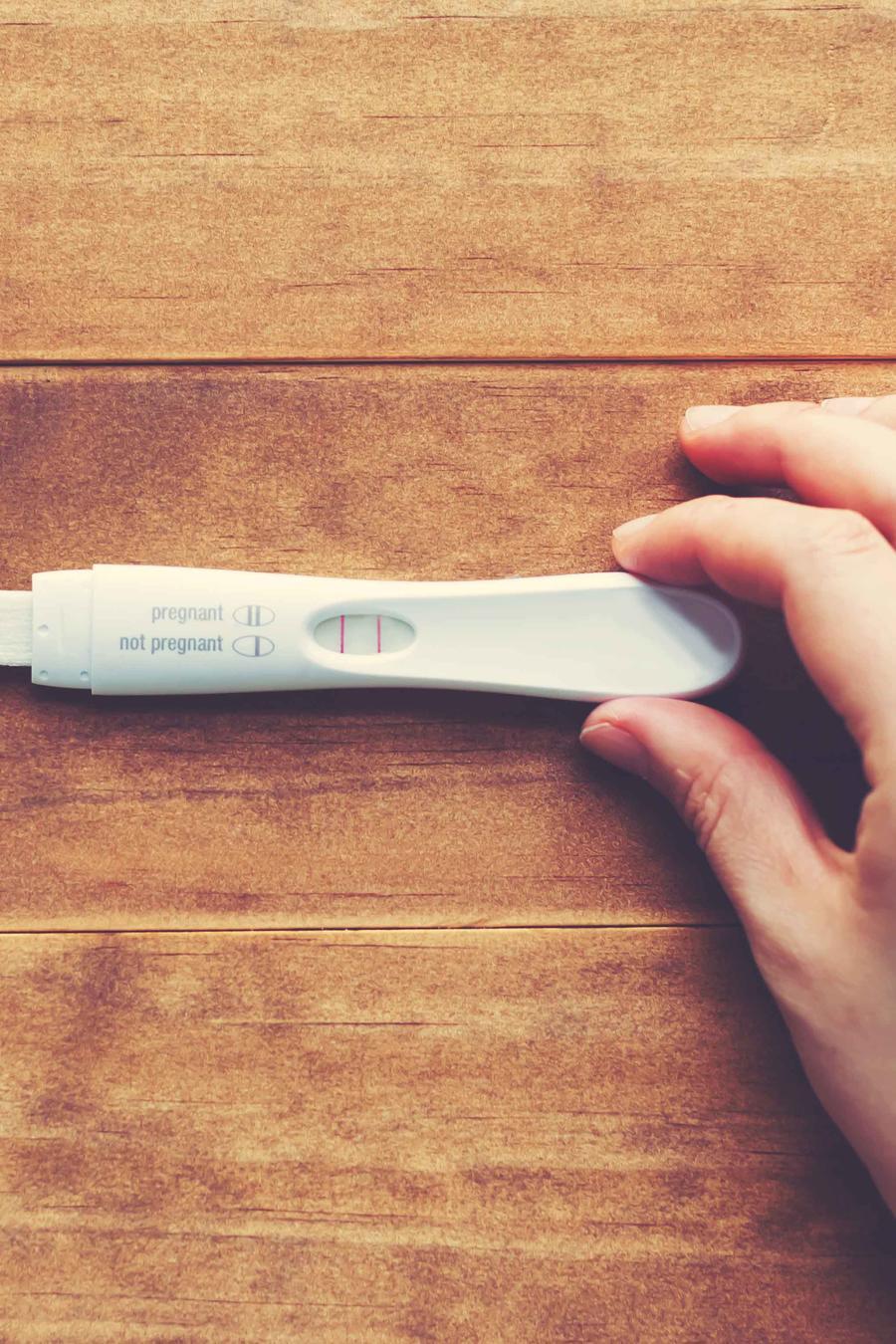 Mano sosteniendo prueba de embarazo sobre madera