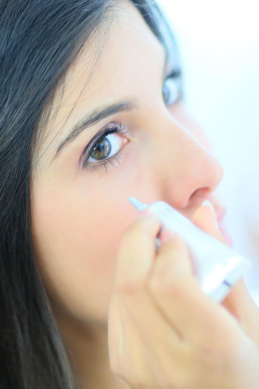 Mujer aplicándose corrector de ojeras
