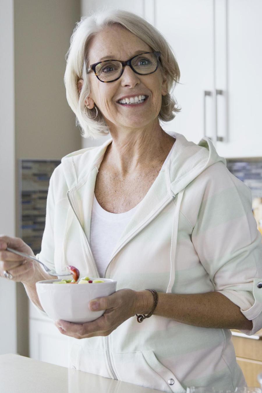 Mujer madura desayunando en la cocina