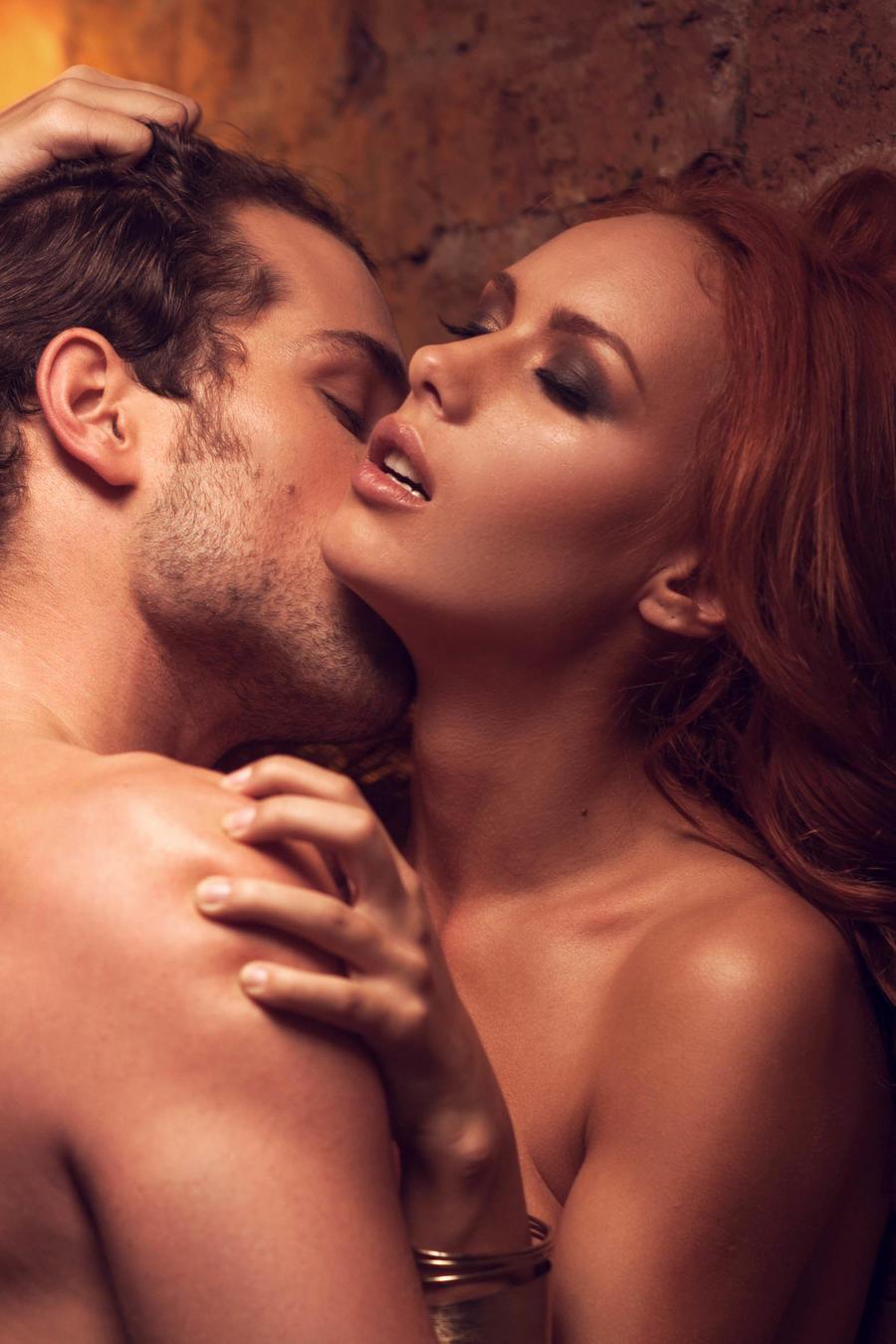Pareja besándose apasionadamente contra la pared