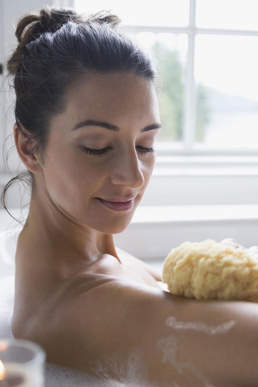 Mujer pasándose la esponja en la bañera