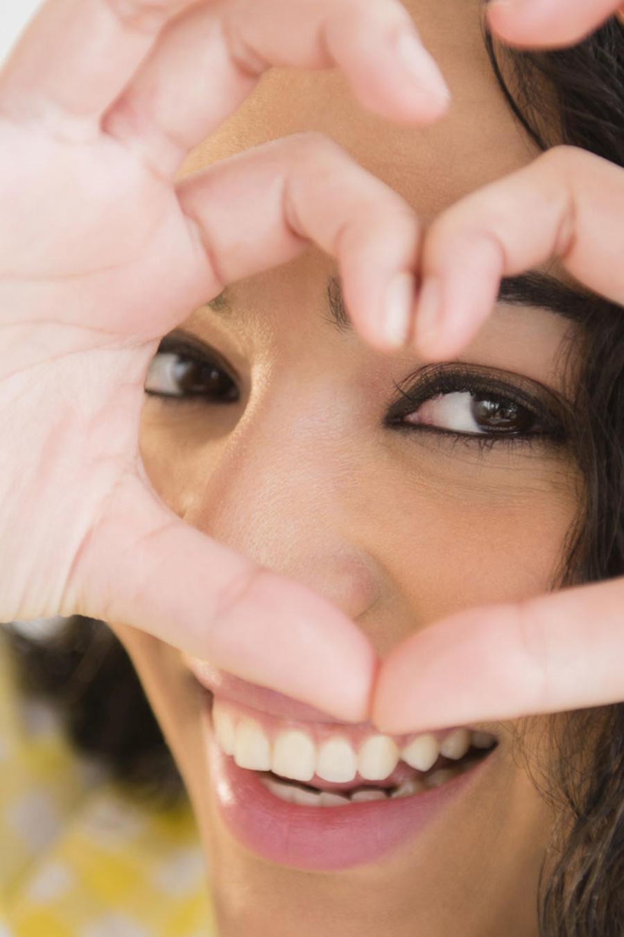 Mujer hispana formando un corazón con las manos sobre su rostro