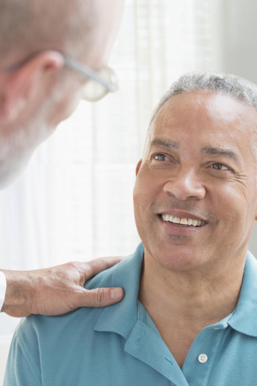 Médico hablando con un paciente hispano en su consultorio