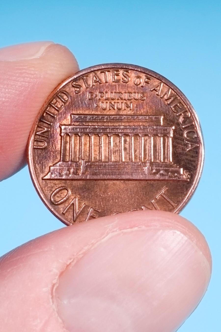 Moneda de un centavo en mano