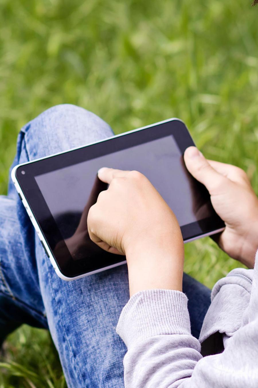 Niño en jardín con tablet