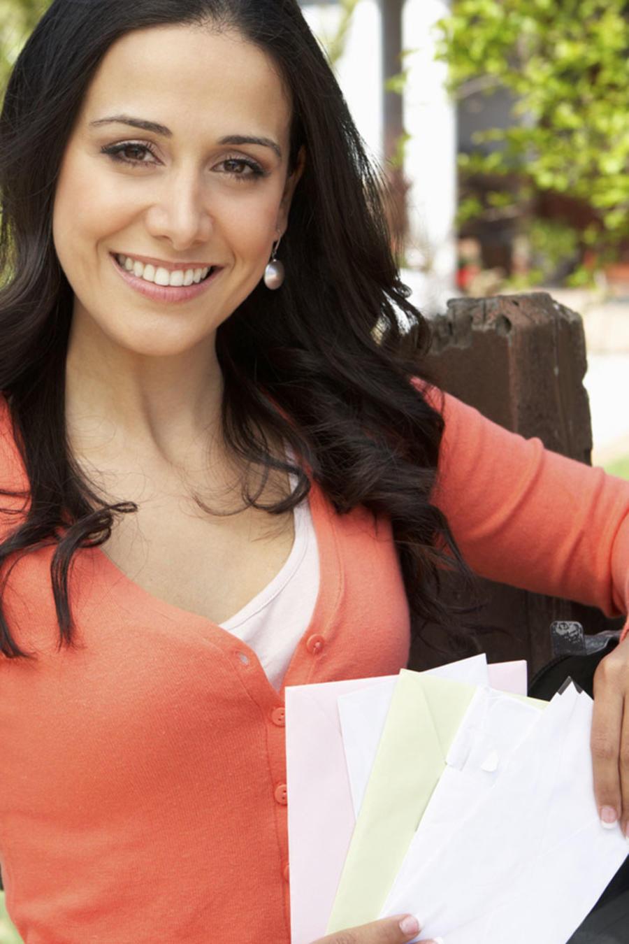 Mujer recibiendo la correspondencia junto al buzón
