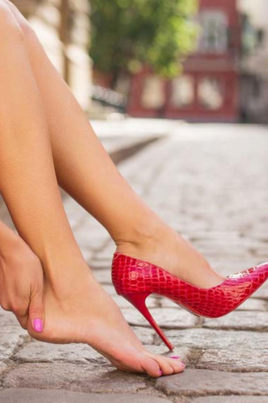 Mujer con dolor en el pie por zapatos de tacón