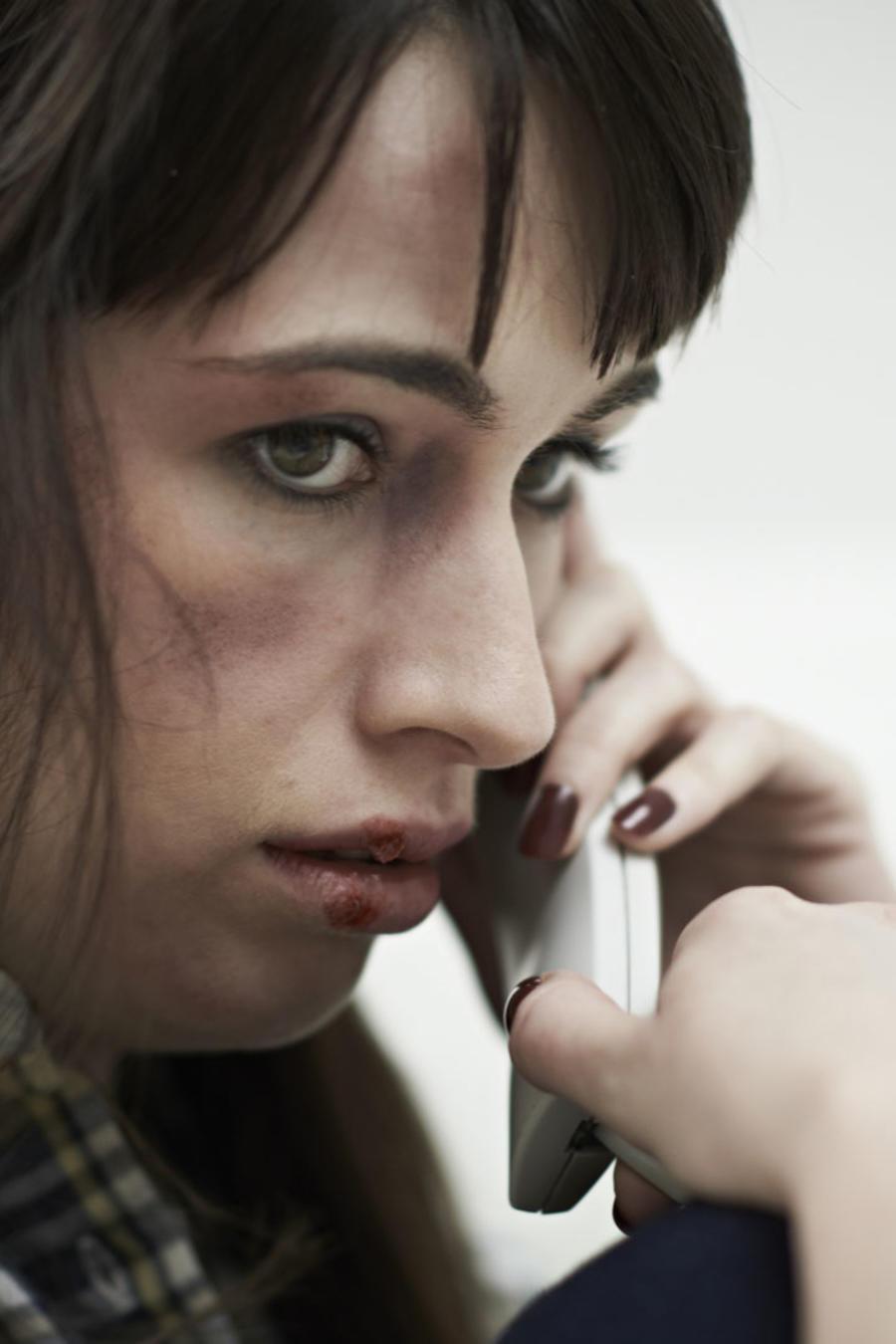Víctima de maltrato pidiendo ayuda por teléfono