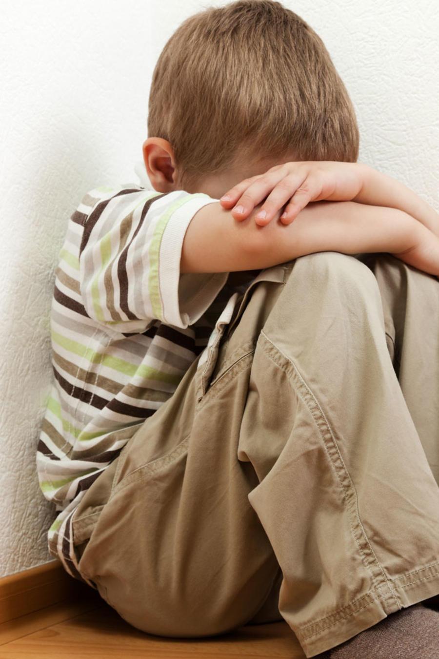Niño sentado en un rincón cubriéndose el rostro