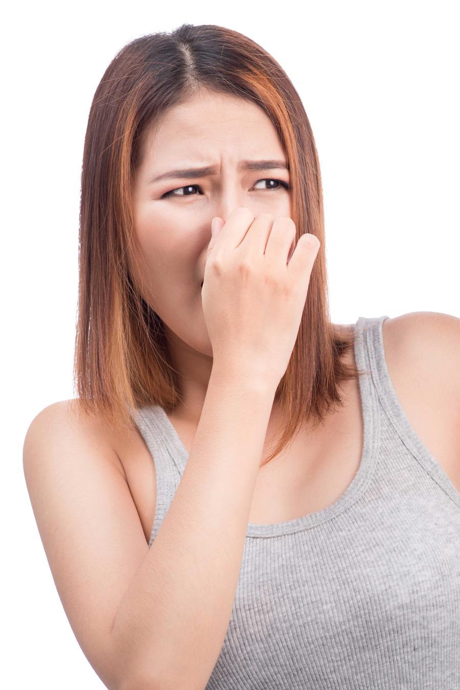 Mujer con la nariz tapada por olor desagradable