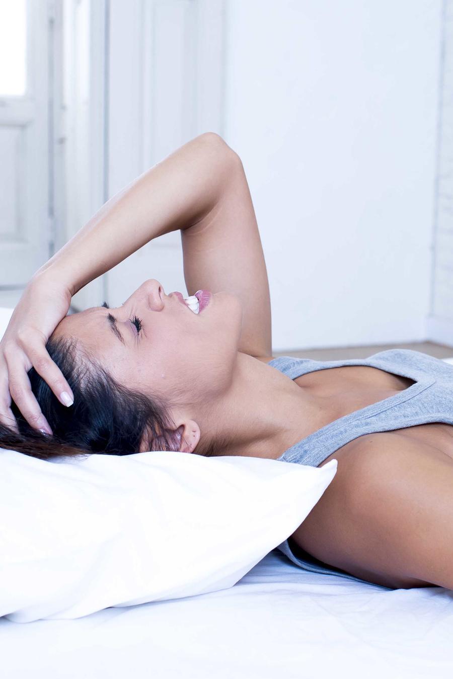 Mujer acostada en la cama con dolor abdominal