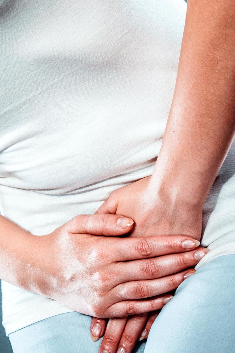 Mujer con las manos en el abdomen por el dolor