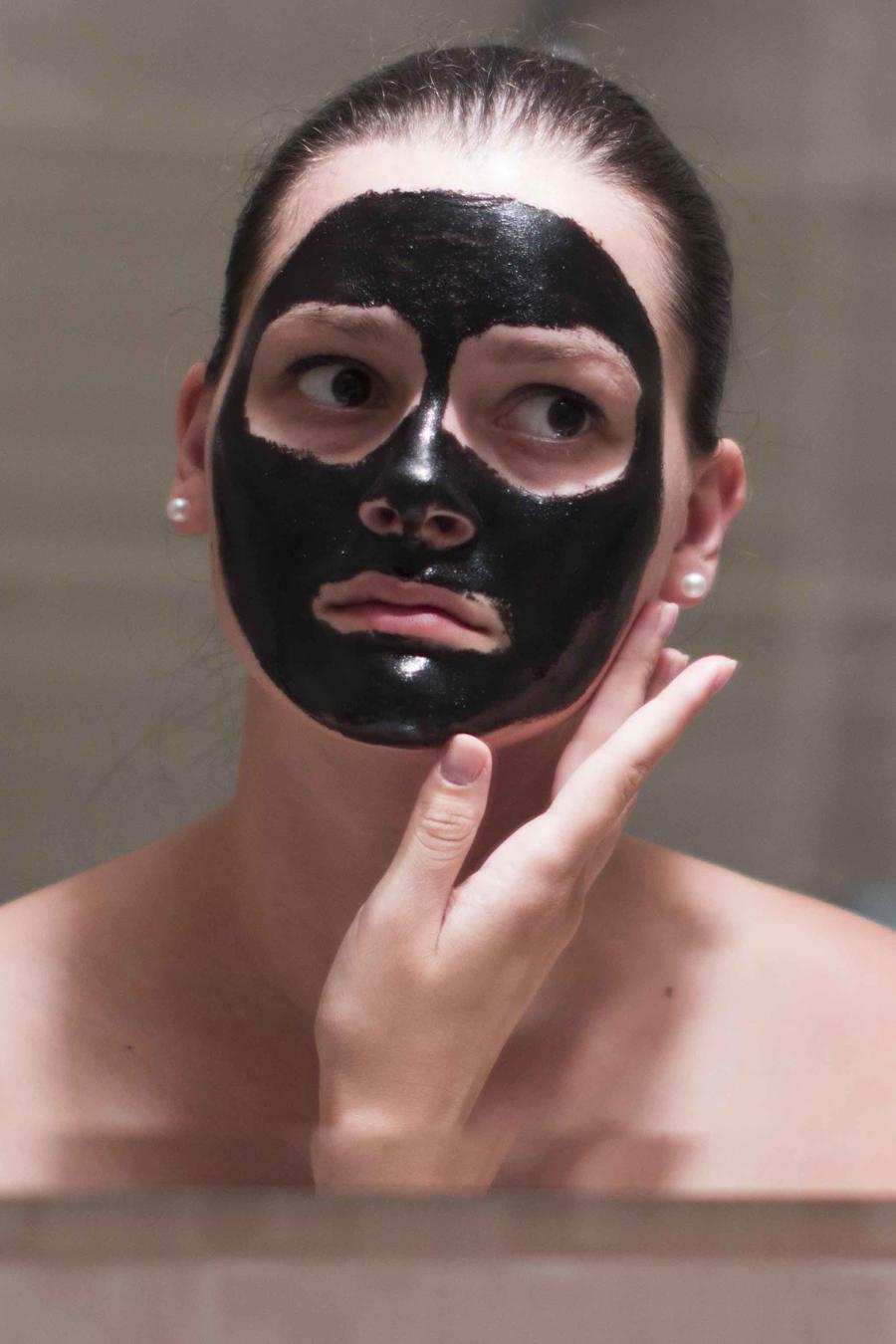 Mujer con mascarilla en el rostro, frente al espejo