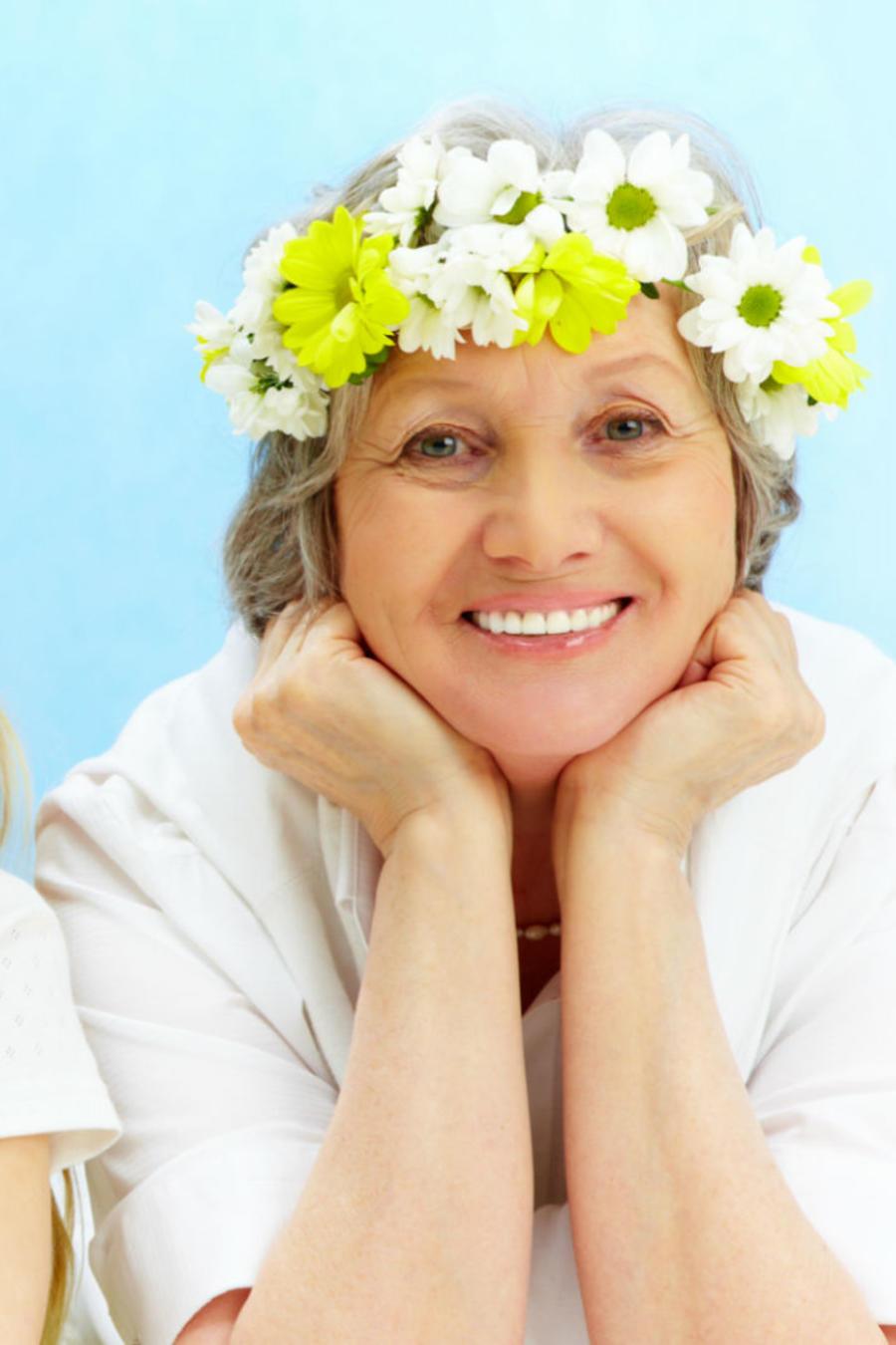 Mamá, hija y abuela sonriendo con una corona de flores en la cabeza