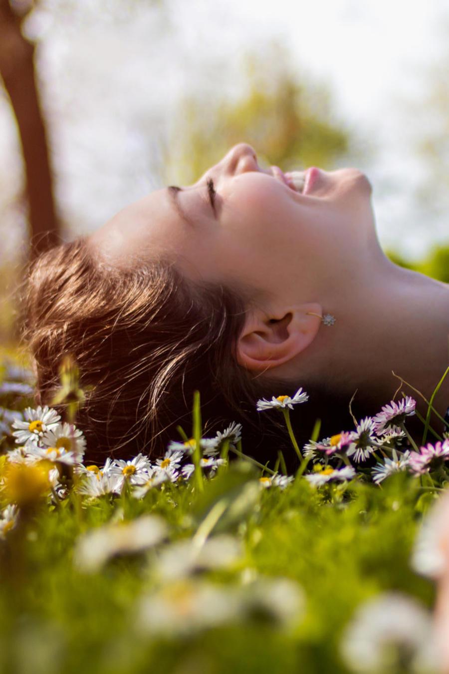 Mujer joven relajada en el césped en primavera