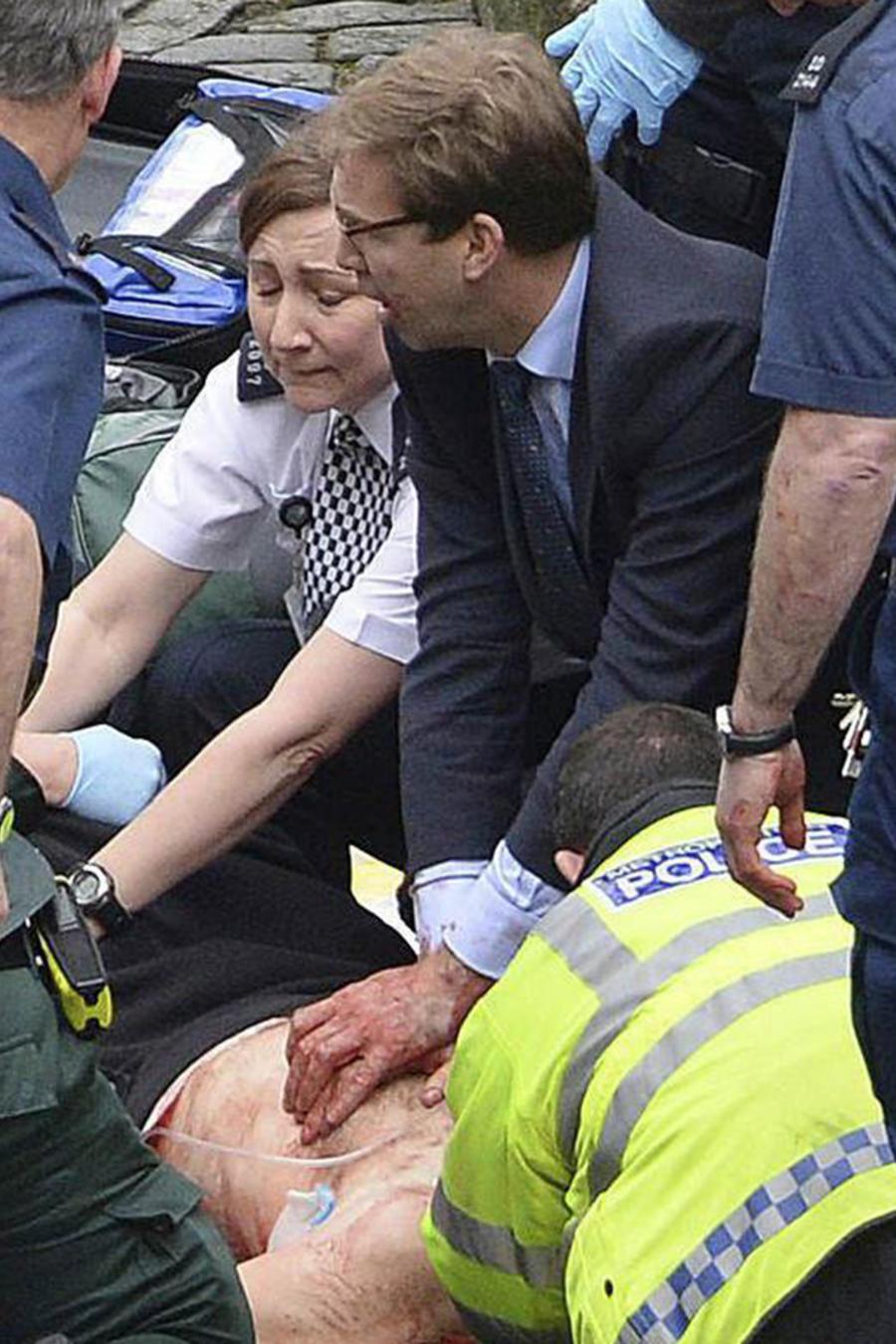 El político británico Tobias Ellwood ayuda a un policía apuñalado durante el ataque terrorista cerca del Parlamento británico el miércoles 22 de Marzo del 2017