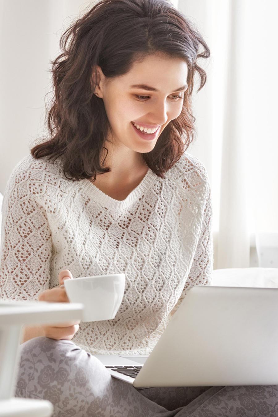 Mujer contenta usando una laptop en la cama