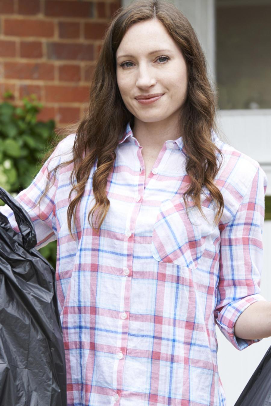 Mujer joven con bolsas de basura en la puerta de su casa