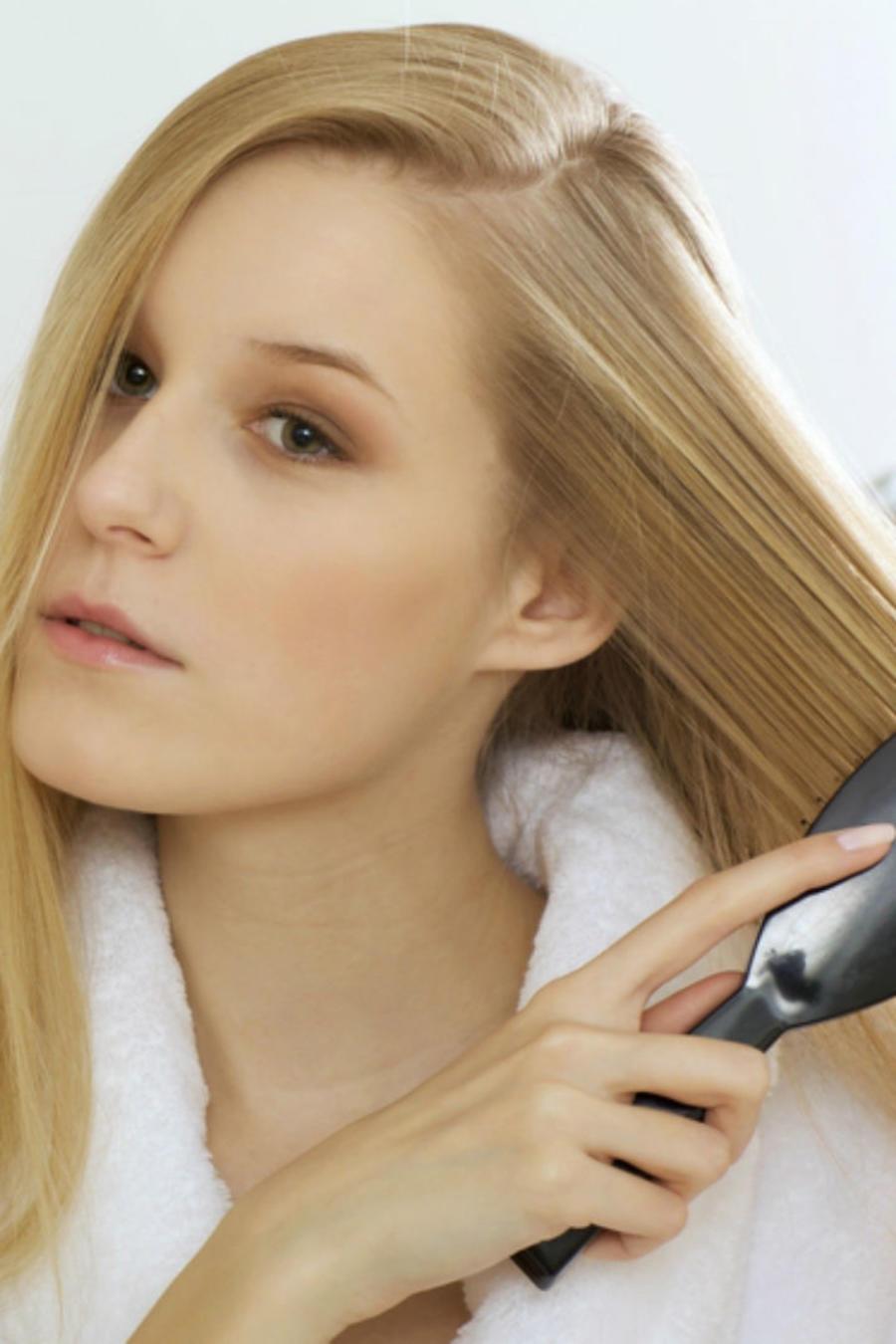 Mujer rubia cepillando su cabello frente al espejo
