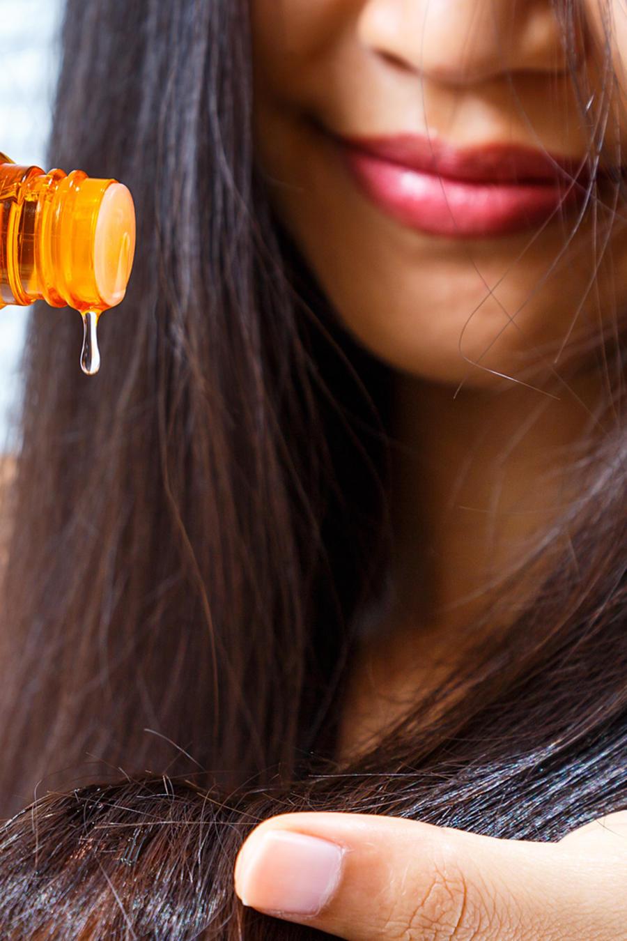 Chica poniendo aceite en su cabello