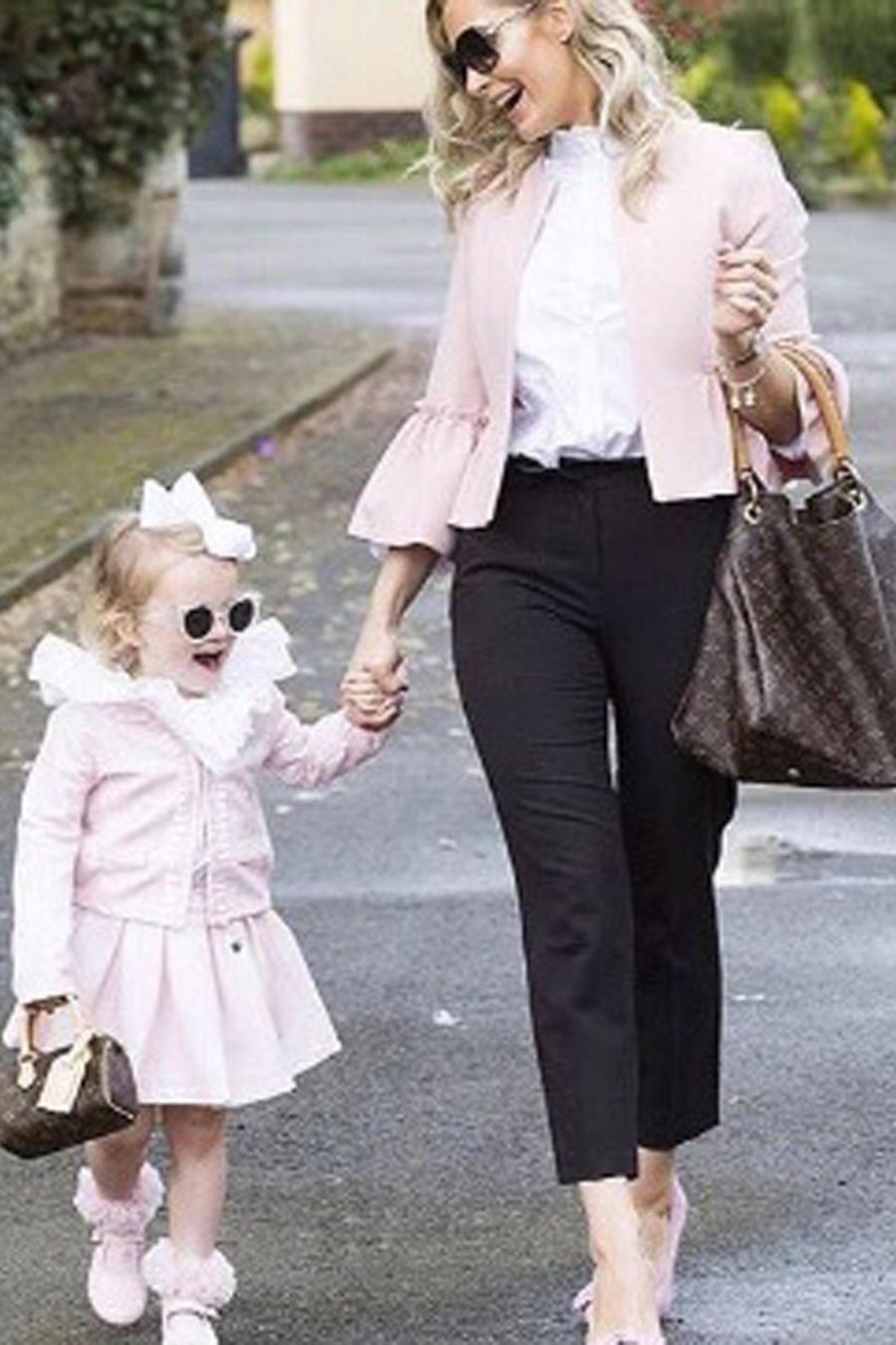 Mamá e hija caminando tomadas de la mano