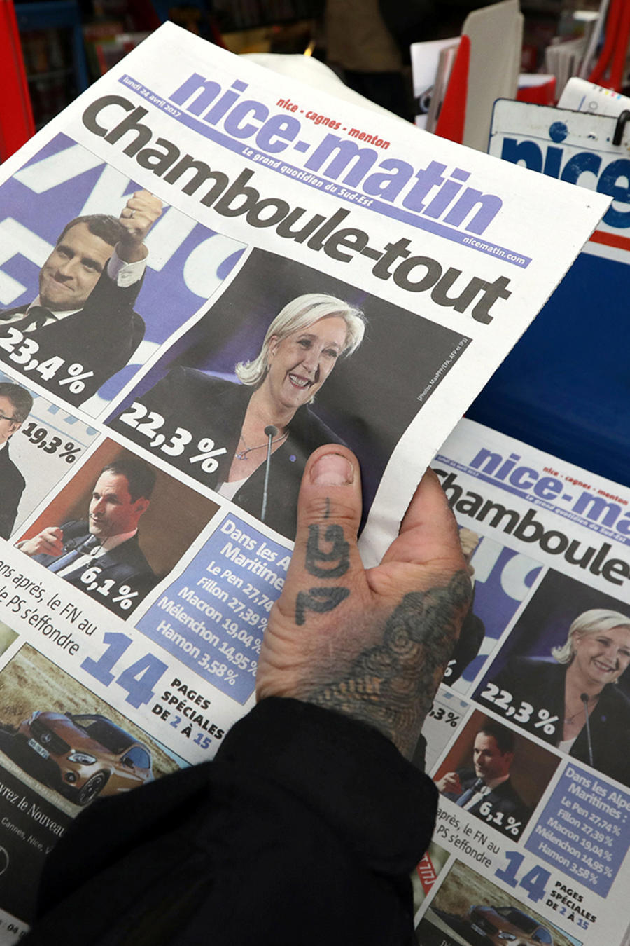 A man holds a copy of the local newspaper with the front page about the results in France's Presidential election, in Nice