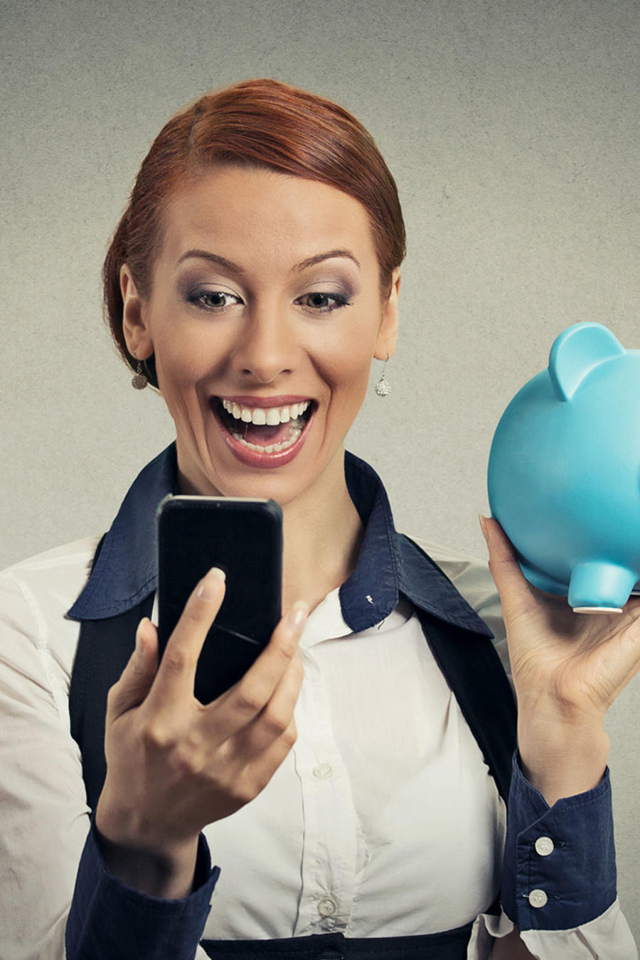 Mujer sostiene celular y alcancía y sonríe