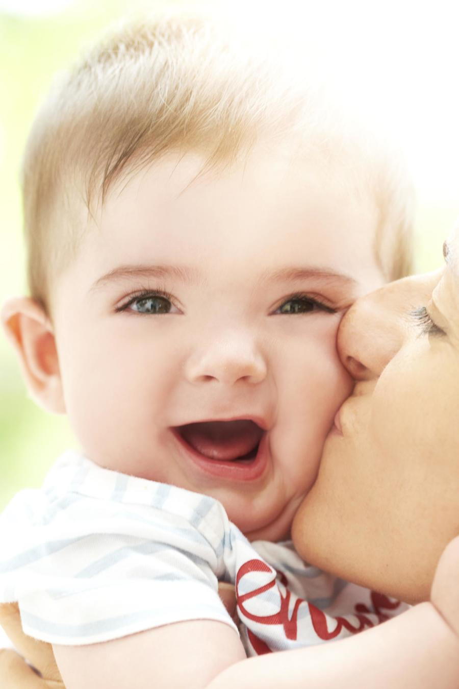 Mother kissing smiling boy toddler on the cheek